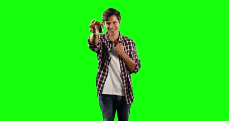 一人 : Portrait of a Caucasian man with short dark hair, wearing a  checkered shirt, smiling and holding car keys, looking straight into a camera on green screen background.