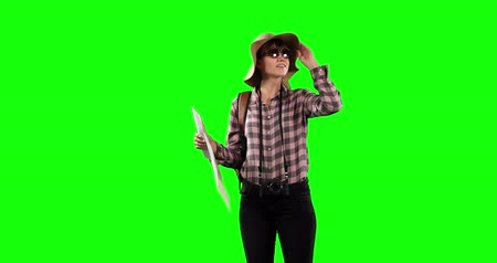turisták : Front view of a happy Caucasian female tourist wearing a checkered shirt a white shirt, sunglasses and a hat, holding a tourist map and a camera hang on her neck on green screen background. Stock mozgókép