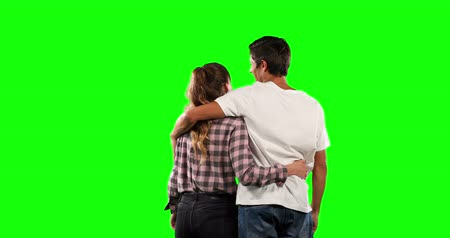 muž : Rear view of a Caucasian couple standing together, interacting, smiling, embracing and pointing up on green screen backround.