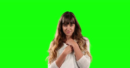 mutlu : Portrait of a happy Caucasian woman with long dark hair, wearing a white shirt, smiling and looking straight into a camera on green screen background.
