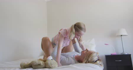 mutlu : Happy Caucasian woman enjoying family time with her daughter at home together, smiling and lifting her daughter above her lying on a bed in their bedroom, social distancing and self isolation in quarantine lockdown, in slow motion.