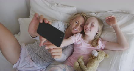 mutlu : Happy Caucasian woman enjoying family time with her daughter at home together, lying on bed in their bedroom, smiling and taking selfies with her smartphone, social distancing and self isolation in quarantine lockdown, in slow motion.