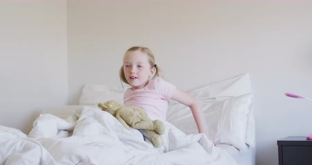 mutlu : Happy Caucasian girl enjoying free time at home, waking up in her bed, next to her teddy bear, social distancing and self isolation in quarantine lockdown, in slow motion. Stok Video