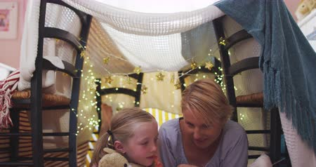 cuarentena : Happy Caucasian woman enjoying family time with her daughter at home together, smiling and talking in a tent in a sitting room, reading a book, with her daughter embracing her teddy bear, social distancing and self isolation in quarantine lockdown, in slo