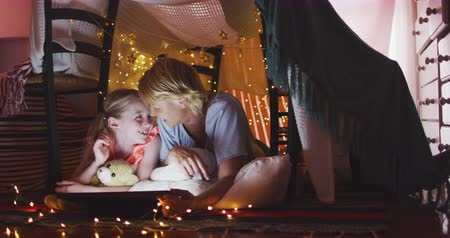 mutlu : Happy Caucasian woman enjoying family time with her daughter at home together, smiling and talking in a tent in a sitting room, reading a book, with her daughter embracing her teddy bear, social distancing and self isolation in quarantine lockdown, in slo