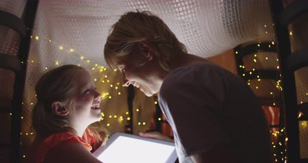 mutlu : Happy Caucasian woman enjoying family time with her daughter at home together, smiling and talking in a tent in a sitting room, using a computer tablet, with her daughter, social distancing and self isolation in quarantine lockdown, in slow motion.