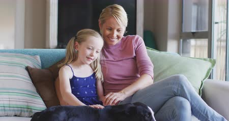 kutya : Happy Caucasian woman enjoying family time with her daughter at home together, sitting on a couch in sitting room and embracing each other, smiling, petting a dog, social distancing and self isolation in quarantine lockdown, in slow motion.