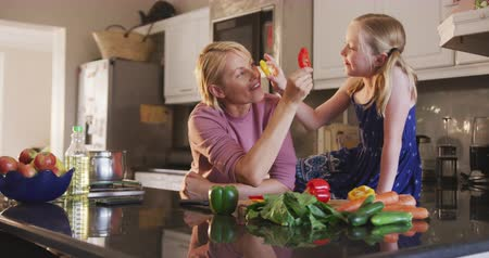 kuchnia : Happy Caucasian woman enjoying family time with her daughter at home together, cooking, preparing a salad and smiling in their kitchen, social distancing and self isolation in quarantine lockdown, in slow motion.