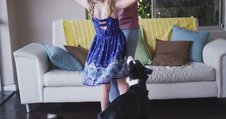 mutlu : Happy Caucasian woman enjoying family time with her daughter at home together, dancing next to a  couch in sitting room and embracing each other, smiling, playing with the dog, social distancing and self isolation in quarantine lockdown, in slow motion.