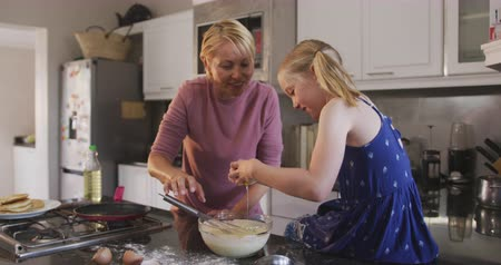 mutlu : Happy Caucasian woman enjoying family time with her daughter at home together, cooking, making pancakes using egg beater and smiling in their kitchen, social distancing and self isolation in quarantine lockdown, in slow motion. Stok Video