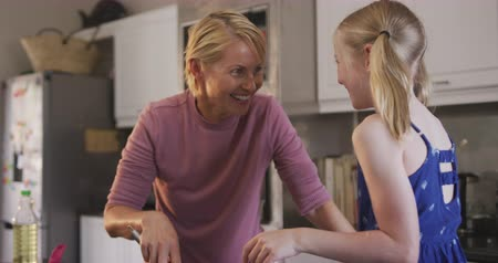 kuchnia : Happy Caucasian woman enjoying family time with her daughter at home together, cooking, making pancakes and smiling in their kitchen, social distancing and self isolation in quarantine lockdown, in slow motion.
