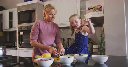 mutlu : Happy Caucasian woman enjoying family time with her daughter at home together, cooking, preparing a fruit salad and smiling in their kitchen, social distancing and self isolation in quarantine lockdown, in slow motion.
