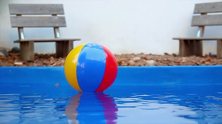 à beira da piscina : Colorful beach ball floating in pool in slow motion