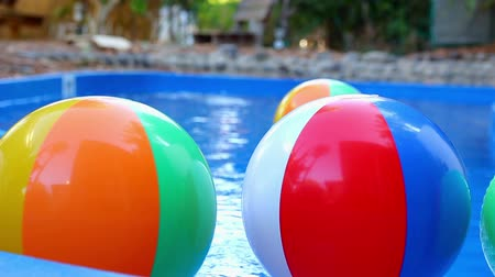 à beira da piscina : Colorful beach balls floating in pool.