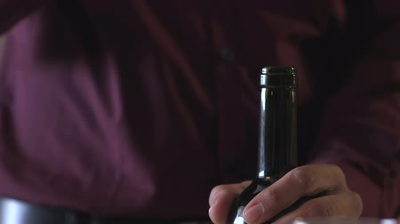 bordo : Man taking the cork out of a bottle of red wine. Stok Video