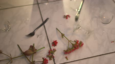 ресторан : Wine glass and red flowers fall on the floor. Fragments of wine glasses, cutlery and red flowers are scattered everywhere. Стоковые видеозаписи