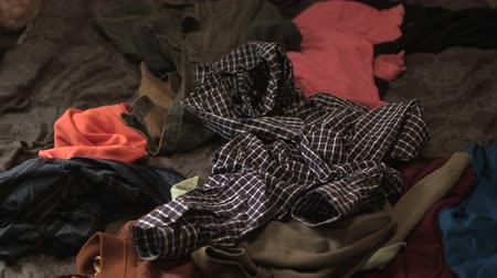dressing room : Clothes thrown on a pile of clothes in bed.