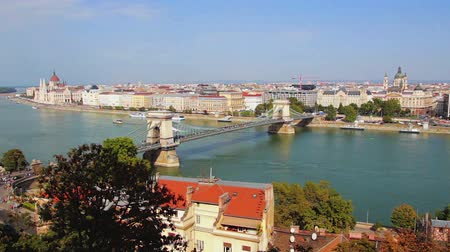 маргарита : Budapest cityscape - View at the Hungarian Parliament, Margaret Island and Szechenyi Chain Bridge. Budapest, Hungary. Vehicles and people in the streets and boats sailing the Danube River. Pan left.