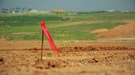 at the stake : Metal survey peg with red flag on construction site Stock Footage