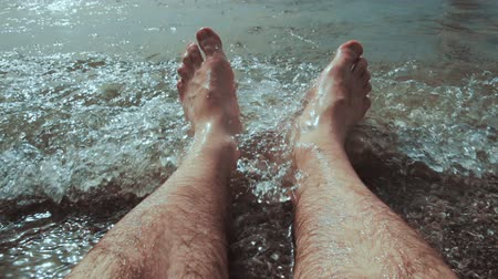 wallow : Caucasian man sitting in water and his legs are washed by the sea waves at the beach Stock Footage