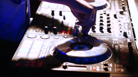 tweak : Hands of DJ tweak various track controls on DJ mixer console at nightclub Stock Footage