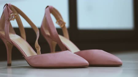 footgear : Pair of classical pink-beige woman wedding shoes on the floor - Changing defocus to focus Stock Footage