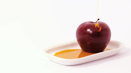 tovah : Pouring honey on red apple on white plate with honey isolated on a white background - slider shot. Symbols of Jewish New Year - Rosh Hashanah.
