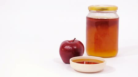 tovah : Red apple and jar of honey and bowl of honey isolated on a white background. Symbols of Jewish New Year - Rosh Hashanah. Slider Shot.