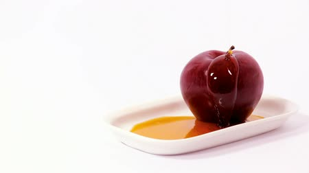 tovah : Cinemagraph of pouring honey on red apple on white plate with honey isolated on a white background. Symbols of Jewish New Year - Rosh Hashanah.