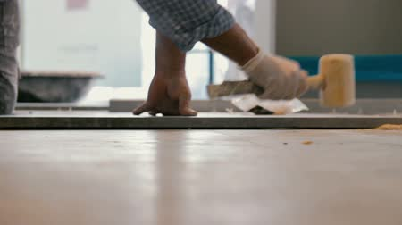 plasterer : Worker putting ceramist tile on the floor. He presses the tile to the floor with a wooden hammer. Stock Footage