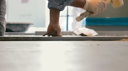 plasterer : Cinemagraph of worker putting ceramist tile on the floor. He presses the tile to the floor with a wooden hammer.