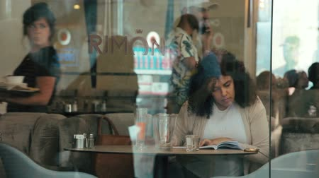 rimon : Jerusalem, Israel - May 11, 2017: Woman sitting in cafe Rimon. She writes notes in a notebook and checking things on her smartphone. People walkng in the street.