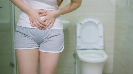 záchod : Pan Shot Of Woman With Urine Urgency In The Toilet