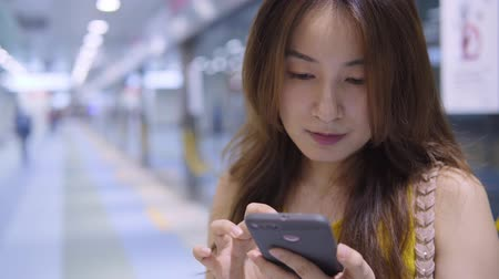 mensagens de texto : Pretty Asian Woman Using Smart Phone At Subway Station