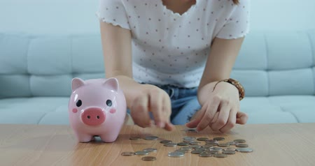 prase : Woman Putting Coins Into Piggy Bank Dostupné videozáznamy