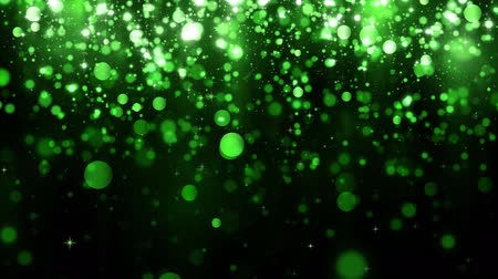 Beautiful glitter light bokeh background. Background with green falling particles. Falling bright confetti and magic light. Seamless loop