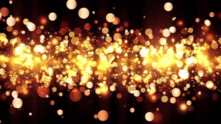 Background with shiny golden particles. Beautiful bokeh light background. Golden confetti with magical shimmering sparkling light. Seamless loop