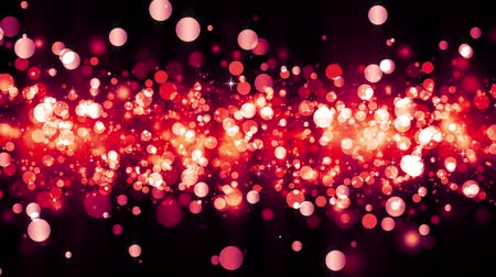 Background with shiny red particles. Beautiful bokeh light background. Red confetti shimmering with magical sparkling light. Seamless loop Stock mozgókép