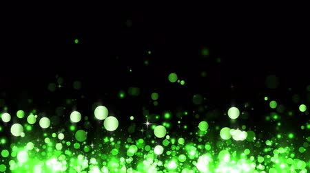 Background with shiny green particles. Beautiful bokeh light background. Glittering rising particles. Green confetti shimmering with magical sparkling light. Seamless loop