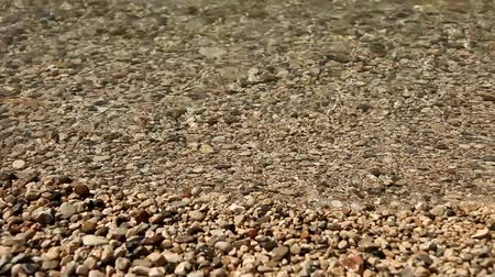 charakteristický : video footage of waves at a lake with pebble stones