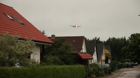 брезент : video footage of deep flying aicfraft over houses in germany, Hamburg Airport Стоковые видеозаписи
