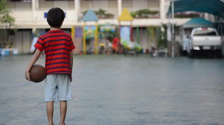 lonely : Little boy waiting to play ball with other children at the playground