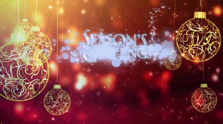 慶典 : Seasons Greetings Swinging Ornaments in Gold features gold swinging Christmas ornaments against a red atmospheric particle background with Seasons Greetings message