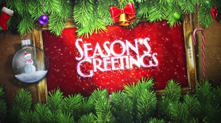 написанный : Seasons Greetings with Pine Branches and Ornaments features an animated hand written Seasons Greetings message in a gold frame with pine branches and swinging ornaments on red Стоковые видеозаписи