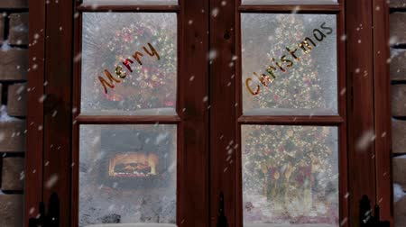 "atmosféra : Merry Christmas Frosted Window features a camera zooming in to a ice frosted window with a Christmas scene inside the house and an animated ""Merry Christmas"" message written in the frost"