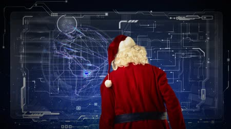 minimalizm : Santa Preparing for the Big Night 4K features Santa looking at a screen with a globe spinning and other technology animations. Stok Video