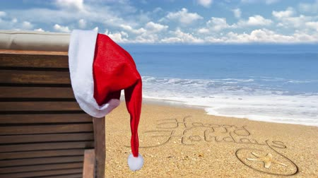 atmosféra : Happy Holidays from the Beach 4K features a beach chair with a Santa hat hanging and gently blowing in the wind with an ocean in the back ground and Happy Holidays written in the sand