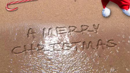 mensagem : Merry Christmas Happy New Year Beach 4K Loop waves washing up on a sandy beach and leaving behind a Merry Christmas Happy New Year message written in the sand in a loop