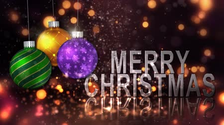 Merry Christmas Ornament Celebration 4K Loop features particles and glitter falling on a surface with metallic words saying Merry Christmas and round ornaments spinning and swinging in a loop Wideo