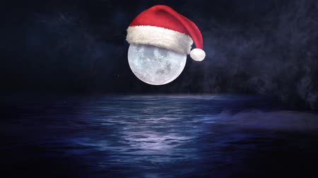 Santa Cap on Moon at Midnight 4K features a full moon with a Santa cap on the moon over water with snow and rolling fog. Wideo